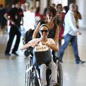 Maria Gadú, de cadeira de rodas, é empurrada pela mulher, Lua Leça, em aeroporto