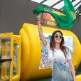Thaila Ayla segura a bandeira do Brasil no jogo de futebol da seleção feminina