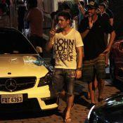 Daniel Rocha sai de boate com taça de champanhe na mão e rodeado de mulheres