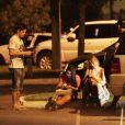 Daniel Rocha troca telefones com mulheres sentadas na calçada