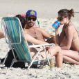 Agatha Moreira bebe uma latinha durante conversa com os amigos na praia