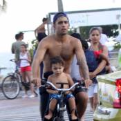 Pedro Scooby anda de bicicleta com o filho Dom na praia do Leblon, no Rio