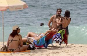Cláudia Abreu passa sábado em família na praia usando maiô retrô