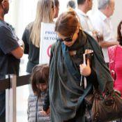 Débora Falabella desembarca com a filha, Nina, e tenta se esconder de fotógrafo