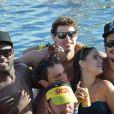 Caio Castro aproveita a festa rodeado de amigos, entre eles, o ator Rafael Zulu, que também usa boné e óculos