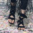 As sandálias que amarram no tornozelo têm saltos altos de acrílico