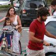 Deborah Secco chega de bicicleta com o marido, Hugo Moura, e a filha, Maria Flor