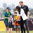 Meghan Markle entrega medalha para menino australiano em evento esportivo