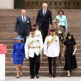 Meghan Markle e Príncipe Harry descem escadaria acompanhados de autoridades australianas