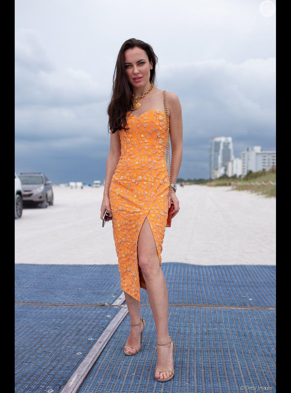 O vestido coral ilumina o visual e garante um toque de cor sutil ao look de festa