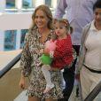 Angélica sorri para o fotógrafo com Eva no colo durante passeio em shopping carioca