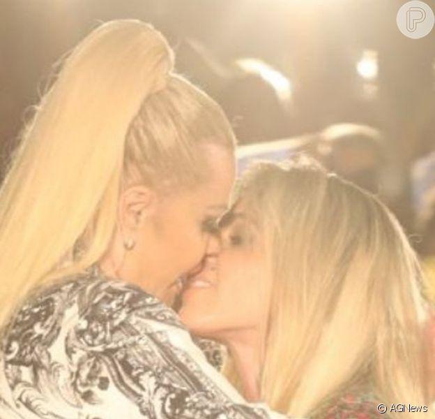 Monique Evans tascou beijão na mulher, a DJ Caca Werneck, durante desfile em homenagem aos 40 anos da grife Yes Brazil