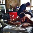 O jogador, que passa as festas de final de ano no Brasil, se distrai com o celular enquanto é tatuado por Filipe Genesi