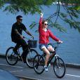 Heather Graham passa mão em árvore durante passeio de bicicleta