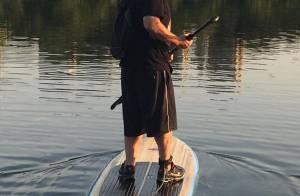 De roupa, tênis e mochila, Leandro Hassum mostra habilidade no stand up paddle