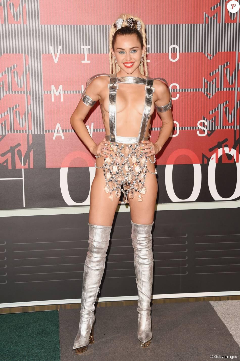Miley Cyrus chegou ao VMA 2015 com um look ousado. A popstar escolheu um suspensório prata, que tampava apenas seus mamilos, e uma tanga de material transparente