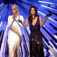 Rita Ora trocou de roupa para apresentar um dos premiados no VMA 2015. A cantora apostou em vestido branco com detalhes em dourado, além de franjas e uma enorme fenda lateral
