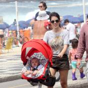 Mariana Gross caminha pela orla do Rio ao lado do marido e do filho, Antonio