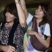 Maria Casadevall busca família em aeroporto de SP carregando gatinha em sling