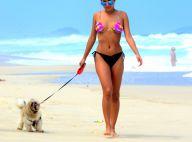 Ex-BBB Munik exibe boa forma de biquíni em praia ao passear com cachorro. Fotos!