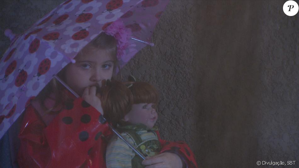 Dulce Maria (Lorena Queiroz), usando capa de chuva e segurando uma boneca,  foge de casa por se decepcionada com o pai, que sempre lhe coloca de castigo, no capítulo que vai ao ar terça-feira, dia 06 de dezembro de 2016, na novela 'Carinha de Anjo'