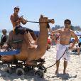 Anderson Di Rizzi e Daniel Rochabrincam com camelo de mentira nesta quinta-feira, 30 de janeiro de 2014, na praia da Barra da Tijuca, Zona Oeste do Rio de Janeiro
