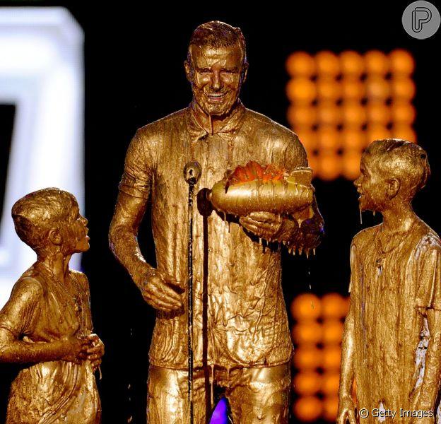 David Beckham toma banho de tinta dourada ao lado dos filhos Romeo e Cruz no prêmio Nickelodeon Kids' Choice Sports Awards, em 17 de julho de 2014