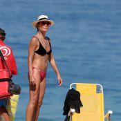Carolina Ferraz vai à praia com o namorado e exibe barriga chapada