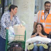 Após alta, Claudia Rodrigues desembarca com cadeiras de rodas e sorridente no RJ