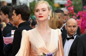 Elle Fanning esbanja sofisticação com vestido fluido e capa em look em tom suave