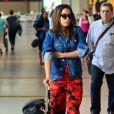 Anitta dobra as mangas da jaqueta Givenchy ao embarcar no Rio