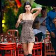 Moda dos anos 2000: vestido de alcinha fina (em animal print), botas longas e bolsa de alça curtinha, você já viu esse look de Kendall Jenner antes?