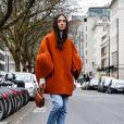 Calça jeans reta é a peça ideal na hora de investir em complementos extravagantes, como o casaco de mangas amplas e as botas bicolores