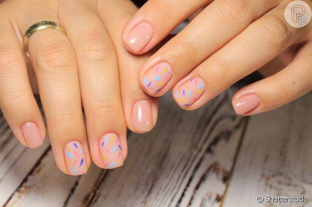 O glitter colorido por cima da base incolor deixa as unhas para o Ano-Novo mais descoladas