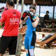 Julianne Trevisol usa t-shirt e legging azul em nunce vibrante para lutar boxe na praia