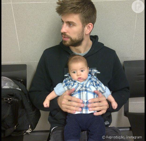 Gerard Piqué segura o filho, Milan, de 2 meses, no colo para esperar o primeiro passaporte do bebê