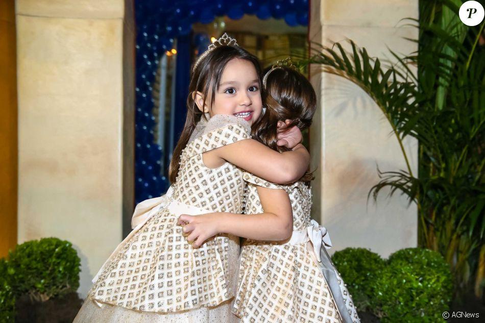 Maya e Kiara se abraçam durante a festa de aniversário de quatro anos