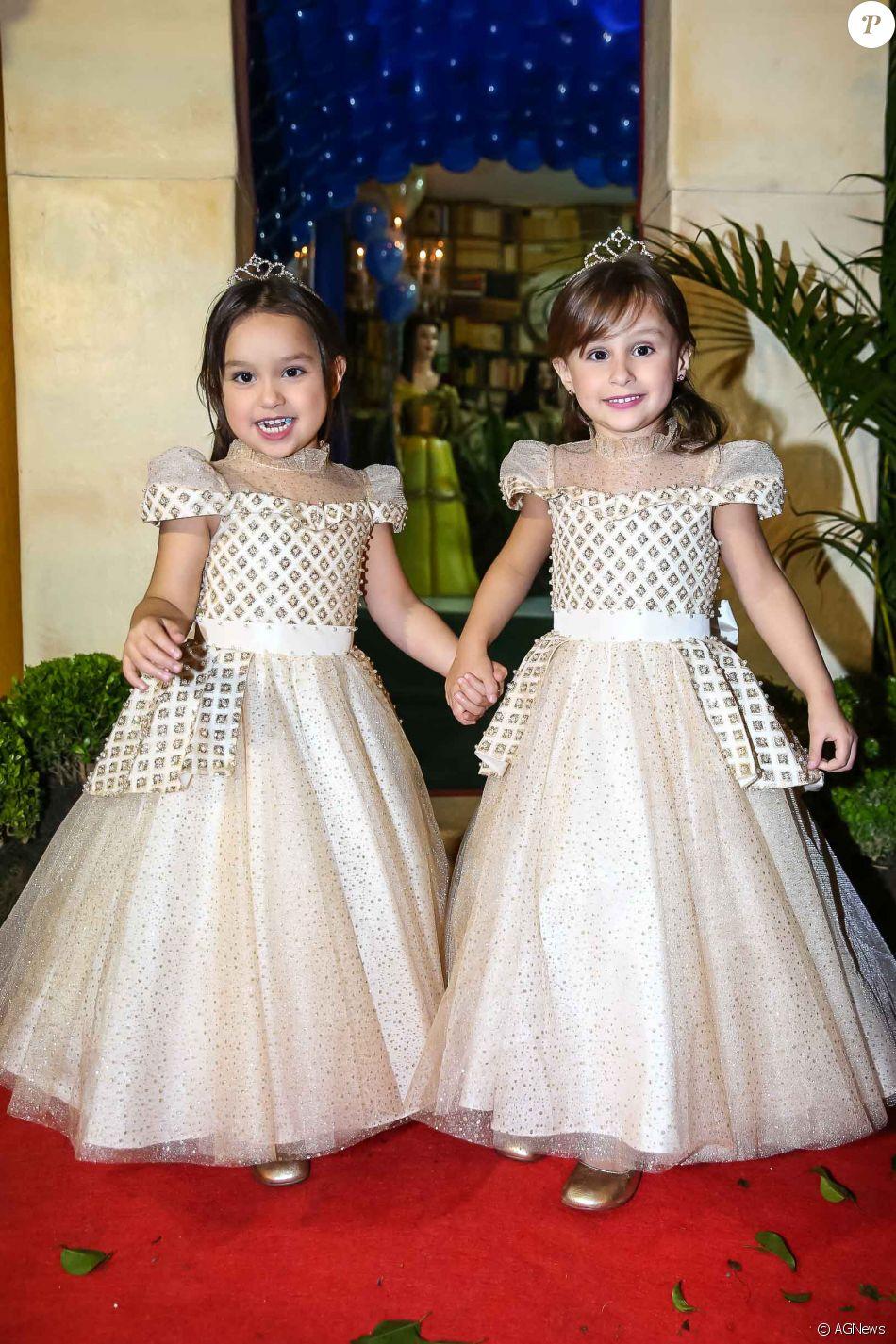 Kiara e Maya, filhas de Natália Guimarães e Leandro, posam de mãos dadas na entrada da festa