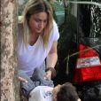 Fernanda Gentil arruma a roupa do filho, Gabriel, em restaurante no Rio de Janeiro