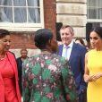 Meghan Markle e Príncipe Harry conversam com participante de evento