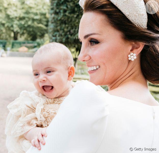 Príncipe Louis foi fotografado sorridente ao lado da mãe, Kate Middleton, em uma nova foto divulgada do batizado do irmão de George e Charlotte