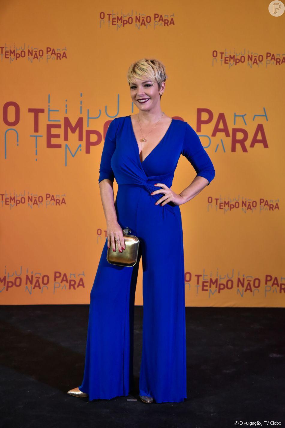 Regiane Alves apostou num macacão azul royal Alphorria e acessórios dourados na festa de lançamento da novela 'O Tempo Não Para', em 16 de julho de 2018