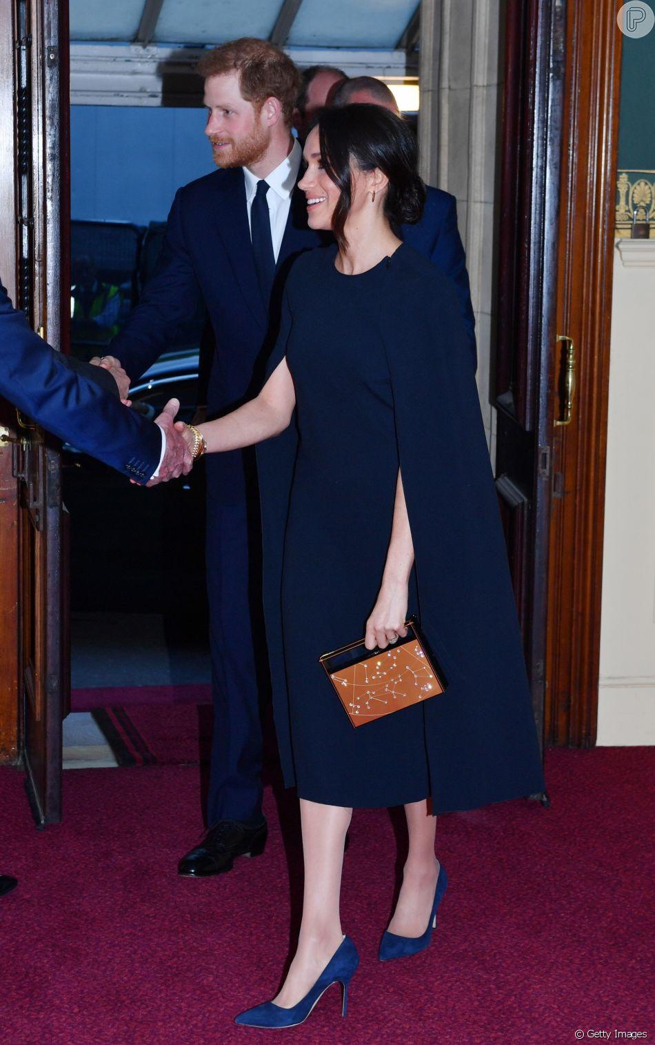 Para a ocasião, Meghan Markle apostou em vestido azul-marinho com capa da  grife Stella McCartney com sapatos azuis Manolo Blahnik e clutch dourada  Naeem ... ddded310f4
