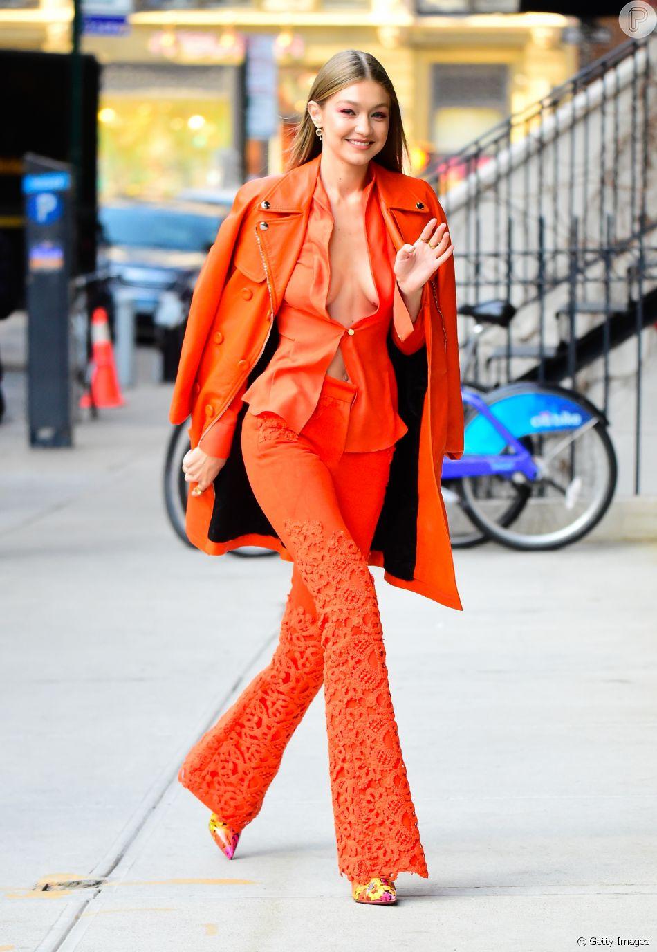 Gigi Hadid em look completo: all orange, decotão, calça flare e high heels.