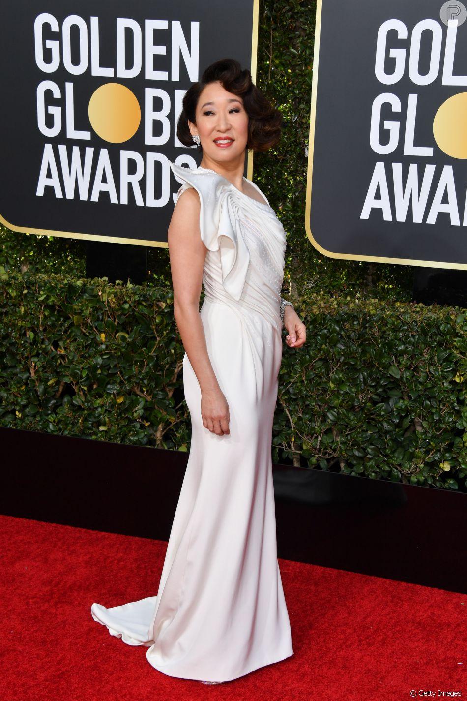 """Sandra Oh, que ganhou o prêmio de melhor atriz por série de Drama por """"Killing Eve"""", escolheu um vestido todo branco para o Globo de Ouro 2019, que aconteceu no dia 6 de janeiro de 2019"""