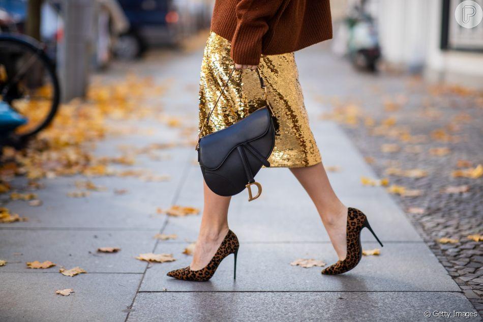 Looks metálicos: saia dourada acendendo o visual junto à Saddle Bag da Dior e scarpin em animal print