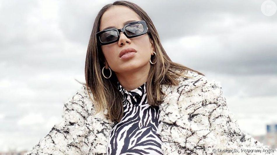 Anitta aposta em maxicasaco e usa óculos acessível em look de frio durante viagem nesta quarta-feira, dia 10 de julho de 2019