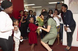 Representatividade! Com look trendy, Meghan Markle ganha flores de criança