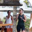 Débora Nascimento confere mensagens em seu celular após a corrida