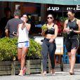 Débora Nascimento e amigas conversam em quiosque, após corrida na praia